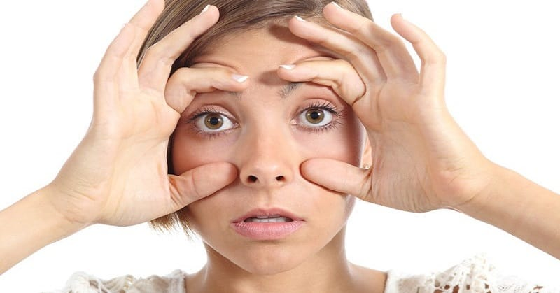 tired woman holding eyes open with fingers