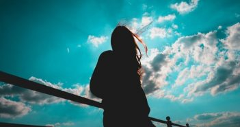 silhouette of young woman against blue sky - illustrating the concept of a free spirit