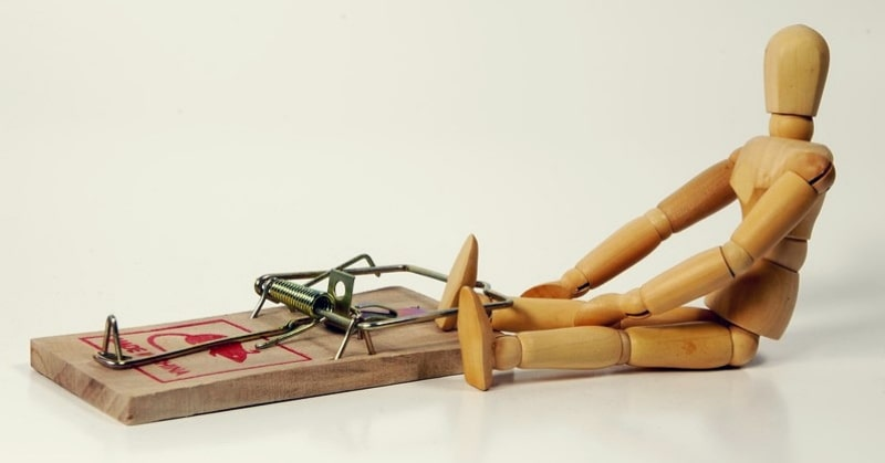 small wooden mannequin with foot trapped in mouse trap
