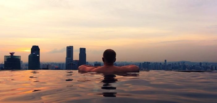 successful man swimming in rooftop pool