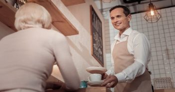 polite waiter serving in a coffee shop