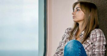 young woman sitting by train window showing signs of anticipatory anxiety