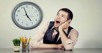 man at work watching clock indicating that he wants to make time go by faster