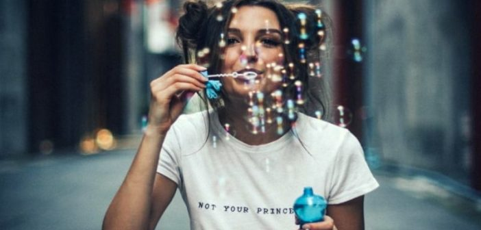 young woman enjoying life by blowing bubbles