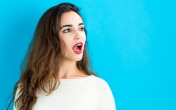 young woman with open mouth as if about to speak, isolated against blue background