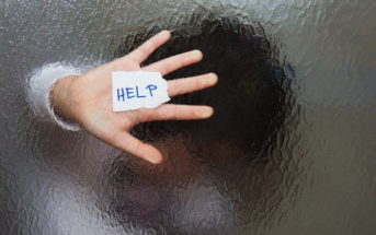 young woman behind frosted glass asking for help