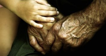 closeup of child holding elderly person's hands and showing them compassion