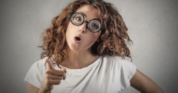 young woman with glasses pointing the finger, blaming others for her problems