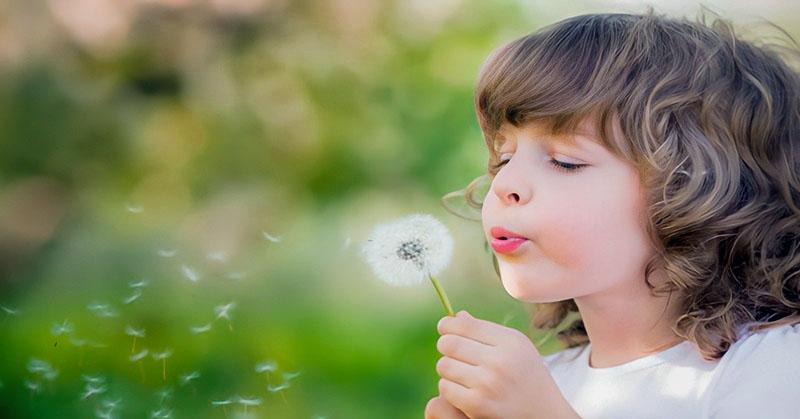 empath child blowing dandelion