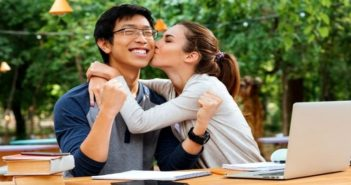young Asian man being kissed on cheek by attractive young woman - illustrating getting out of the friend zone