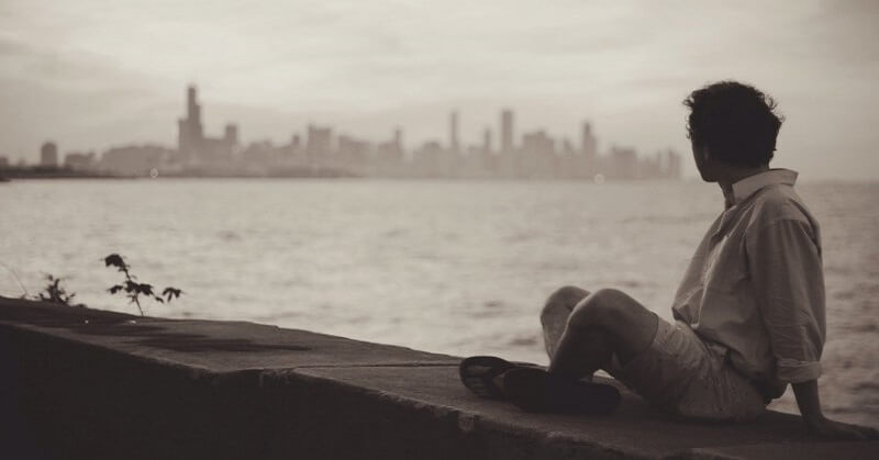 man looking across sea at city asking what is the purpose of life?