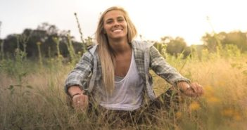 emotionally independent woman smiling sitting in grassy field