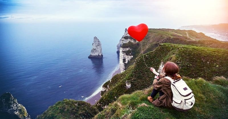 girl on cliff holding heart balloon illustrating that she's never been in a relationship or in love before