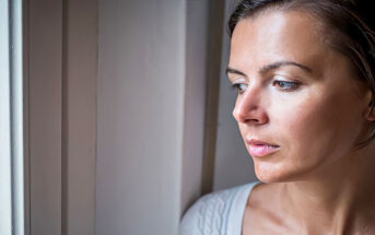 sad pensive woman looking out of window illustrating self-denial