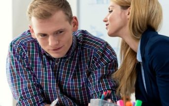 woman whispering in male coworker's ear signalling sexual tension