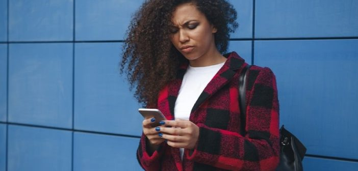 young woman looking at phone with confused expression illustrating the concept of breadcrumbing