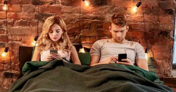 couple sitting in bed staring at their phone illustrating effects of social media on relationships