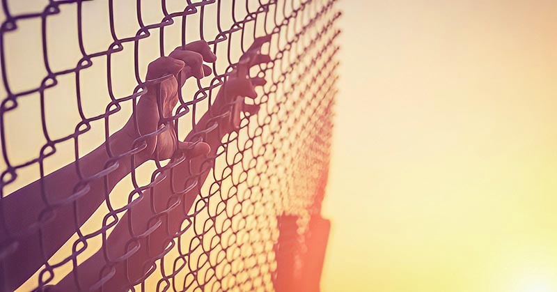 hands on chain link fence illustrating feeling trapped in life