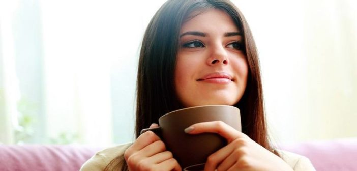 woman drinking coffee with smile on her face showing that she has become happy again