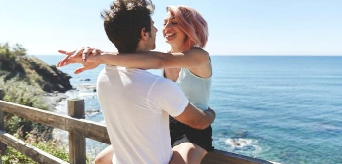 young couple smiling with ocean in the background illustrating infatuation versus love