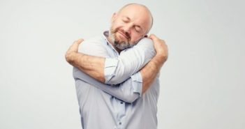 man hugging himself illustrating being kind to yourself