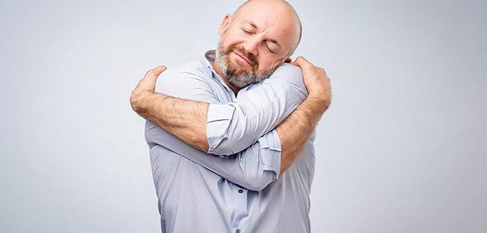 man hugging himself illustrating being kind to yourself