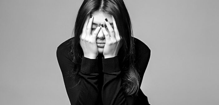 black and white image of young woman with hands across face illustrating that life is hard