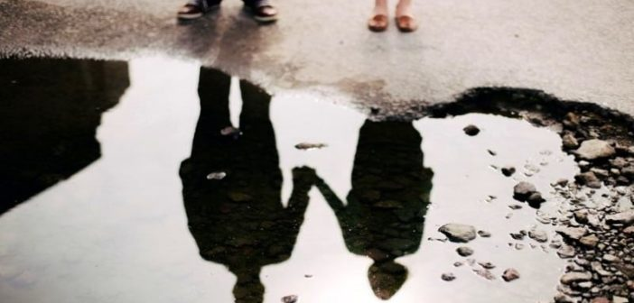 reflection in a puddle of couple holding hands illustrating a situationship