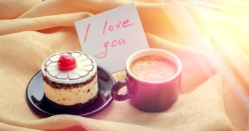 cake, cup of coffee and love note laid on bed illustrating surprising your girlfriend
