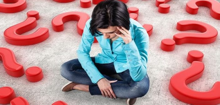 young anxious girl sitting on floor surrounded by question marks illustrating decision anxiety