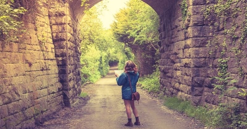 woman with map walking down country path illustrating trying to find yourself