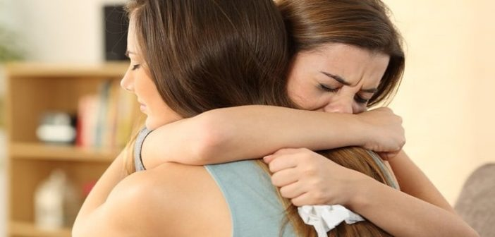 young woman hugging her crying friend and helping her through a breakup