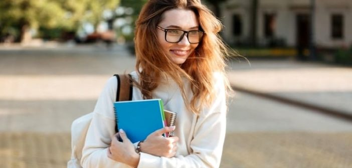 young woman with glasses holding books illustrating a reserved person
