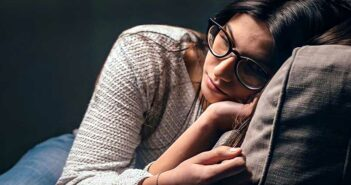 young woman with glasses looking anxious while sitting on the couch - illustrating the Sunday Night Blues