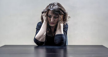 depressed woman holding head in her hands