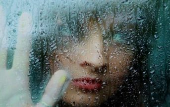 woman looking through rainy window having lost faith in humanity