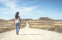 woman walking desert path into the horizon illustrating setting a goal