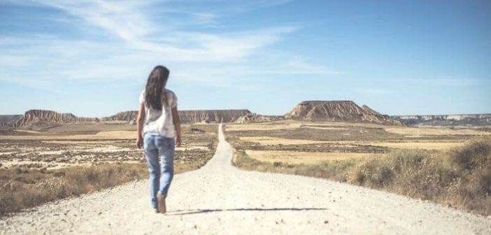 woman walking desert path into the horizon illustrating setting a goal