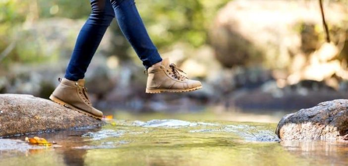 woman jumping over stream illustrating being proactive