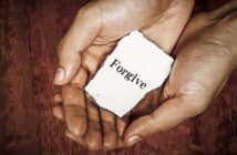 hands held together holding piece of paper with forgive written on it