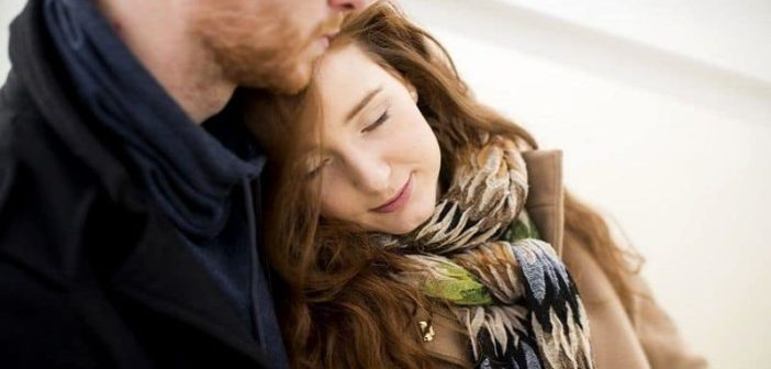 young woman cuddled up to boyfriend and feeling loved