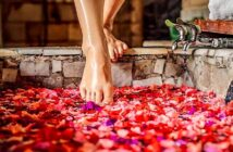woman stepping into bath with rose petals - example of how being selfish is good