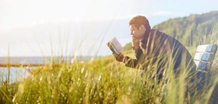 a man reading book alone in nature illustrating the concept of giving him space