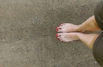 woman's bare feet on stony ground