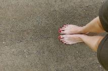 woman's bare feet on stony ground