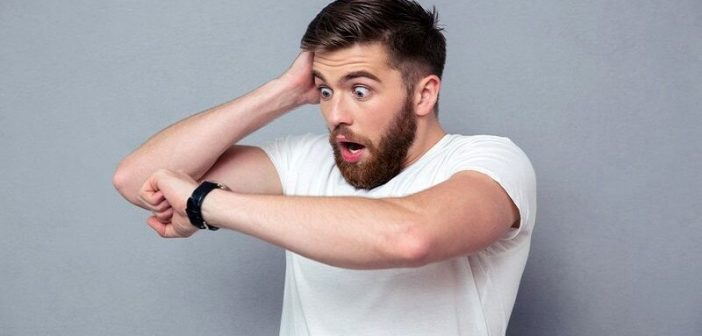 shocked man looking at watch to illustrate the importance of being on time