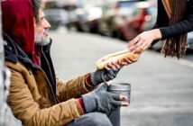 woman handing food to homeless person - illustrating being generous
