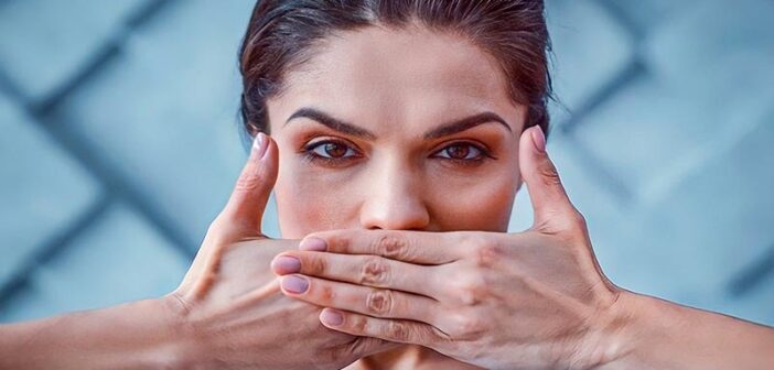 Woman with her hands over her mouth as she tries to stop saying sorry so much