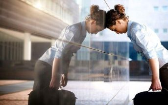 businesswoman leaning head against glass building illustrating burnout and its symptoms