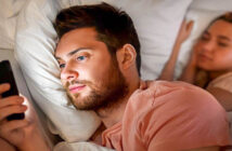 man having emotional affair by texting someone else whilst girlfriend sleeps in the background